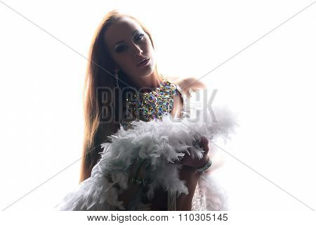 Beautiful Woman In White Stage Costume With Boa And Bling-bling Necklace Over White Light