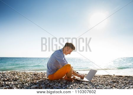 Man walking with laptop computer by the sea coast