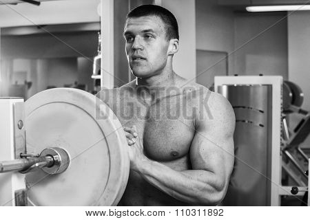 A man performs an exercise with a barbell. Young weightlifter in the gym.