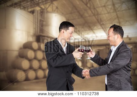 Two Asian Business Man Holding A Glass Of Wine And Handshaking