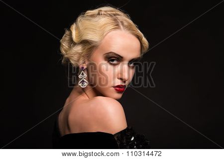 Portrait photo model on a dark background. Stylish makeup and jewelry.