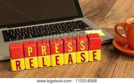 Press Release written on a wooden cube in a office desk
