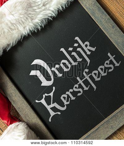 Merry Christmas (in Dutch) written on blackboard with santa hat