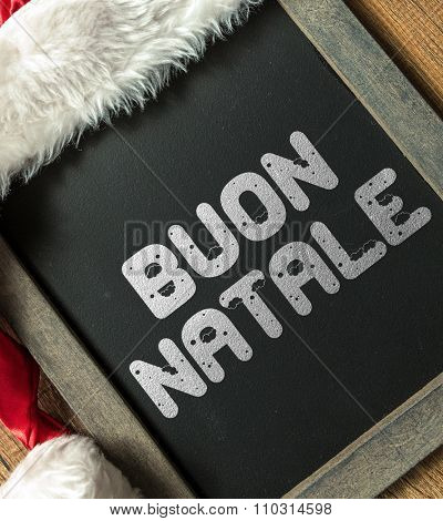 Merry Christmas (in Italian) written on blackboard with santa hat
