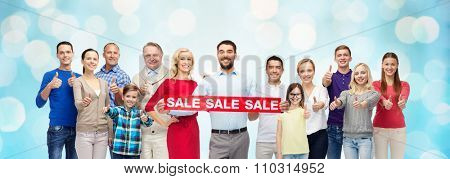 gesture, shopping and people concept - group of smiling men, women and kids showing thumbs up and holding red sale sign or banner over blue holidays lights background