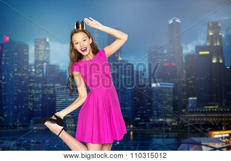 people, holidays and fashion concept - happy young woman or teen girl in pink dress and princess crown over night singapore city background