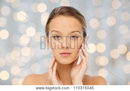 beauty, people and health concept - young woman with bare shoulders touching her face over holidays lights background