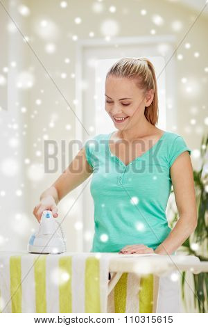 people, housework, laundry and housekeeping concept - happy woman with iron and ironing board at home over snow effect