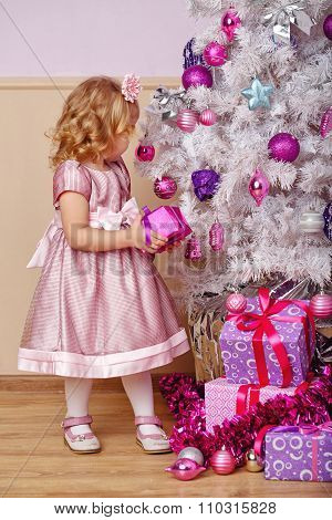 Little Girl Lays Out The Gifts Under Christmas Tree.