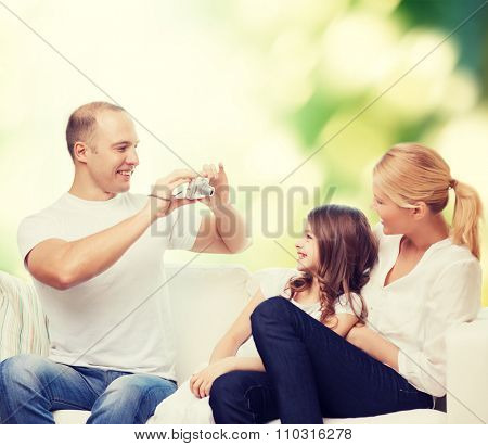 family, technology, ecology and people - smiling mother, father and little girl with camera over green background