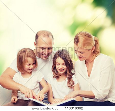 family, childhood, ecology and people - smiling mother, father and little girls reading book over green background