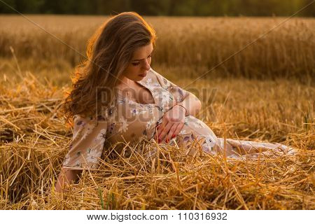 Beautiful young pregnant woman in a dress middle of wheat fields
