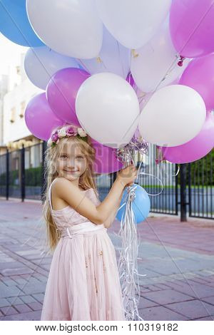 Little five-year girl in a pink dress holding balloons, against background of summer street