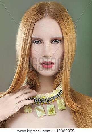 Beautiful red-haired girl with freckles, long straight hair and a necklace around her neck. Beauty f