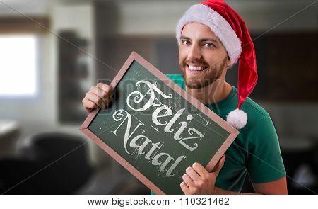 Feliz Natal (Merry Christmas in Portuguese) written blackboard by a man