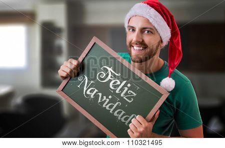 Feliz Navidad (Merry Christmas in Spanish) written blackboard by a man