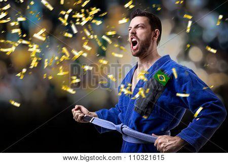 Brazilian judoka fighter holding a medal in the stadium
