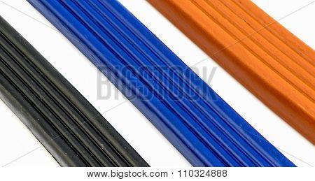 3 Pieces Of Plasticine Orange, Blue And Black Background