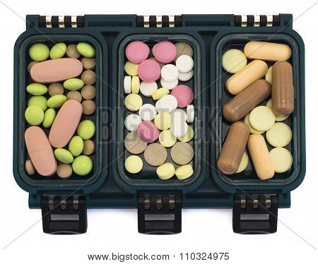 Multi-colored Pills In Green Box Organizer Isolated On White