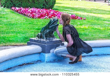 Young Woman Kisses Frog Sculpture.