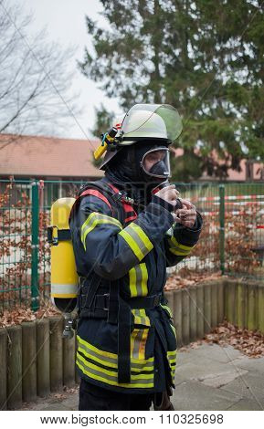 Firefighter with breathing apparatus and oxygen cylinder in action