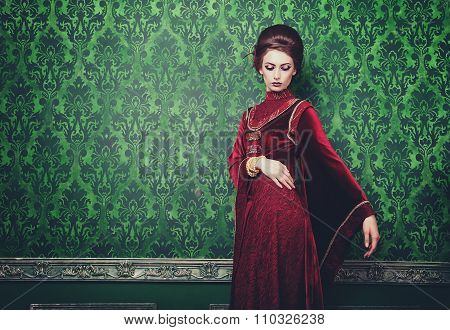 Woman In Old Styled Clothes On Green Vintage Pattern Background