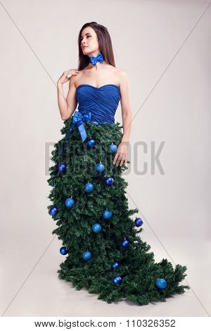 Girl In Christimas Tree Fantasy Dress On Grey Background