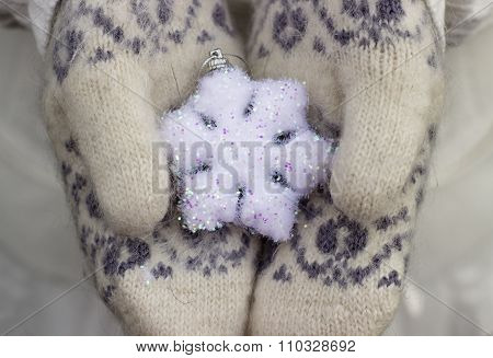 Female hands close up in knitted wore mittens holding white snowflake outdoors
