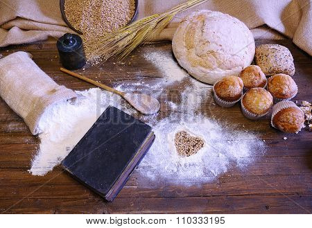 Different Types Of Bread, Fruit Cakes And Scattered Flour On Wooden Table