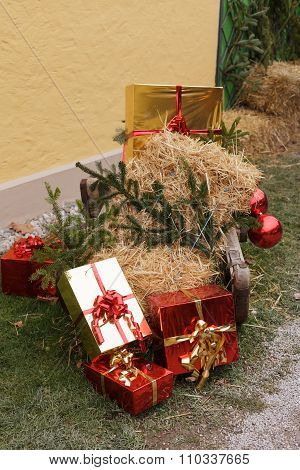 Christmas packages with straw and pine branches on a sled