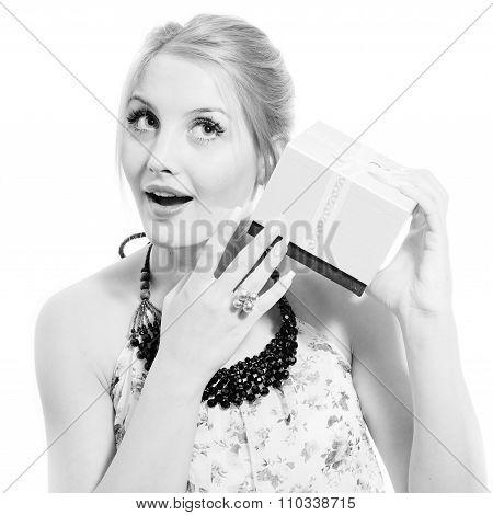 beautiful blond young woman having fun listening to gift box