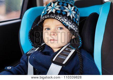 Adorable toddler boy sitting in safety car seat