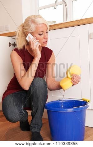 Woman Mopping Up Leaking Sink On Phone To Emergency Plumber