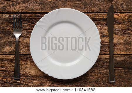 Fork And Knife Lying Near Empty White Plate
