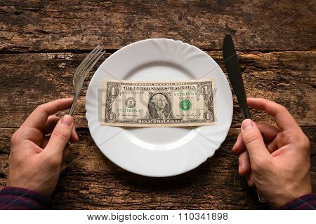 Man Holding A Knife And Fork Next To The Plate Which Is One Dollar