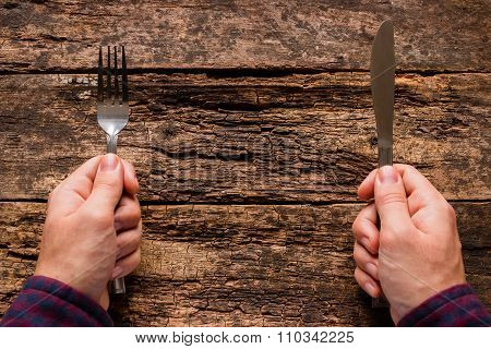 Man Holding A Knife And Fork On A Wooden Background