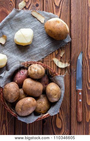 Unpeeled And Peeled Potatoes In A Basket And A Knife On A Wooden Background