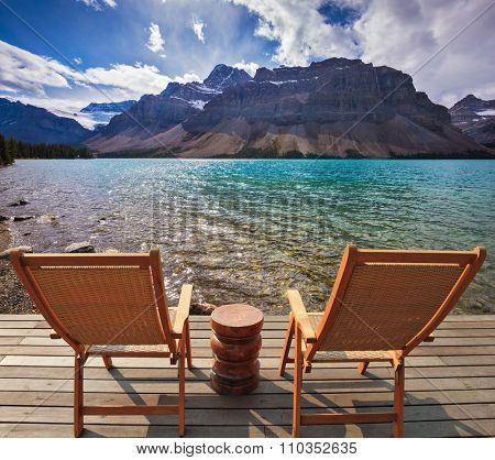 Cold autumn day in the Rocky Mountains of Canada. On the wooden platform there are two deckchairs beside a beautiful lake