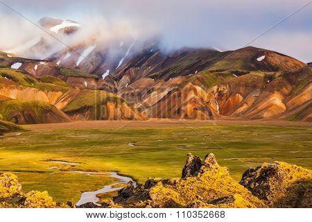 National Park Landmannalaugar, Iceland. Pink dawn in the Arctic. Striped mountains of rhyolite covered sunshine