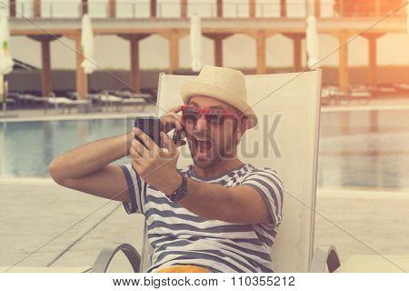 Angry man on the swimming pool with cellphone.
