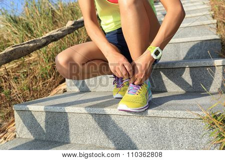 fitness woman runner tying shoelace on mountain stairs