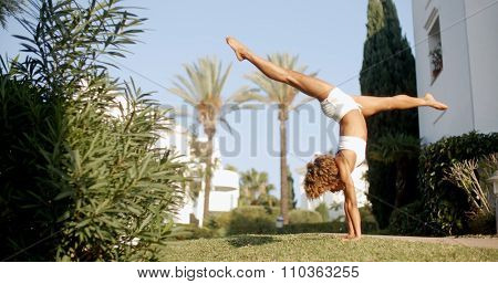 Girl doing a handstand on grass field. Slow motion shot of young african woman doing stunts on grass.