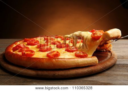 Pizza Margherita and removed slice on brown background