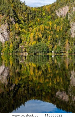 Autumn Reflections Of A Steep Tree Covered Cliff In A Lake