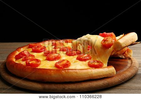 Pizza Margherita and removed slice on dark background
