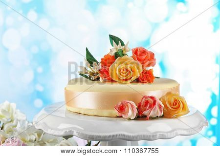 Cake with sugar paste flowers, on light background