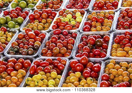 Fresh red, orange, yellow, and green grape tomatoes at farmers' market.