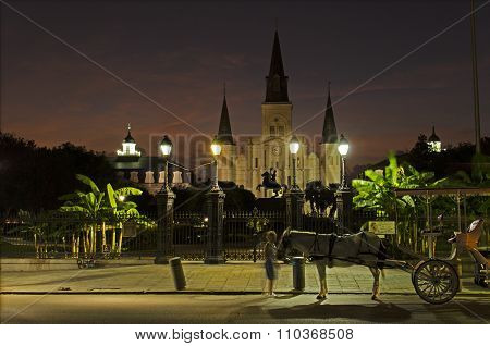 St Louis Cathedral and Jackson Square in New Orleans at night time with a horse and carriage.