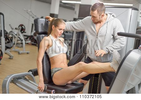 Shot of male personal trainer assisting woman leg press