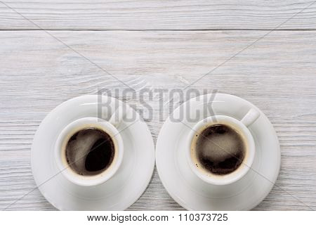 Two Cups Of Coffee With Foam On A White Wooden Table